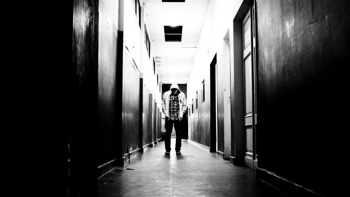 Hombre encapuchado en medio de un pasillo para ilustrar el relato Némesis