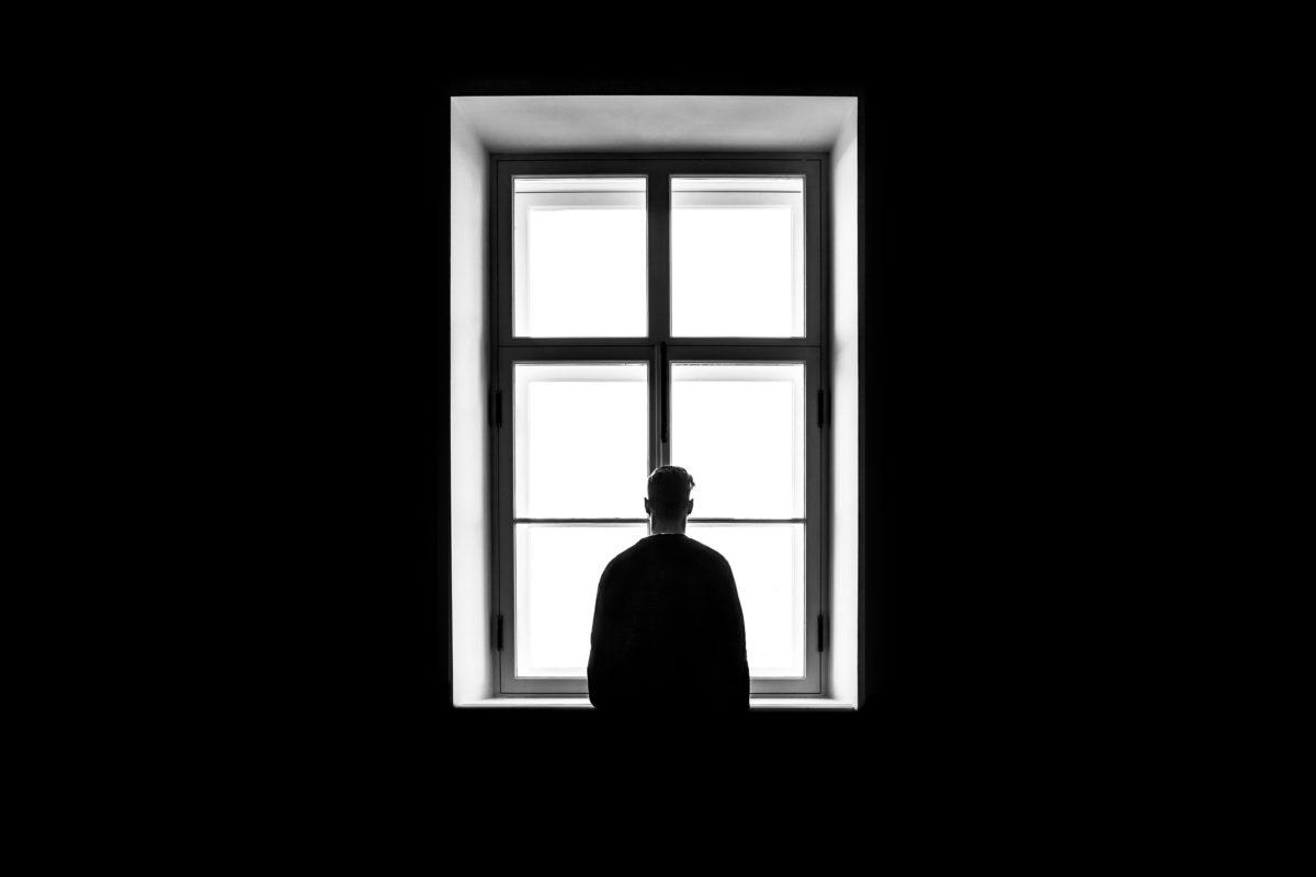 Hombre de espaldas mirando por la ventana