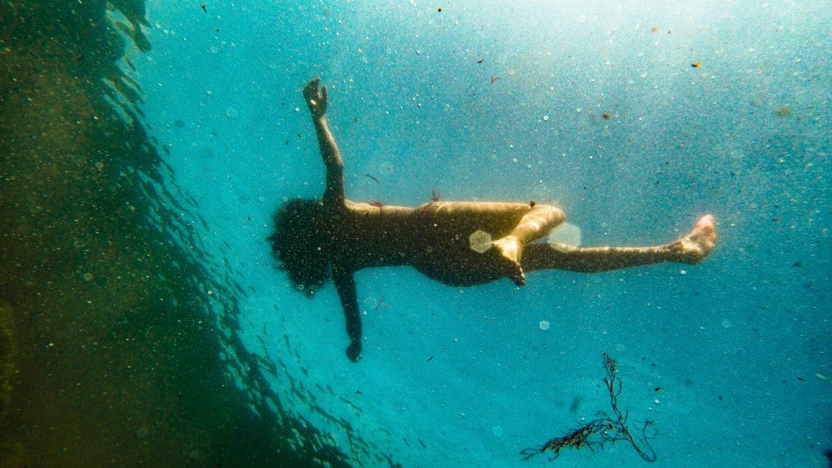Una mujer flotando en el mar, vista desde abajo.
